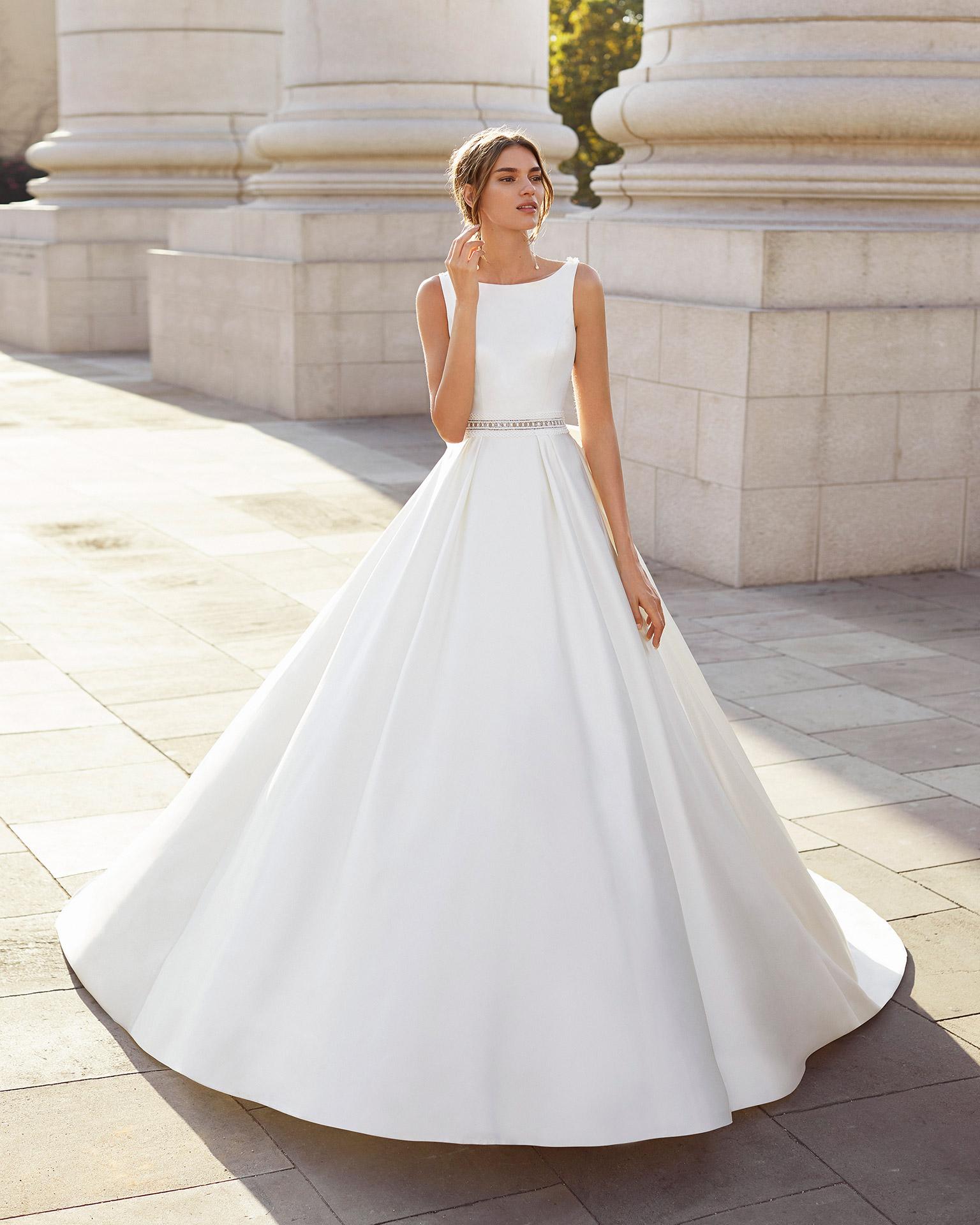 Vestido de novia estilo clásico de raso, encaje y pedrería. Escote barco y espalda transparente de encaje pedrería y lazo. Colección  2021.