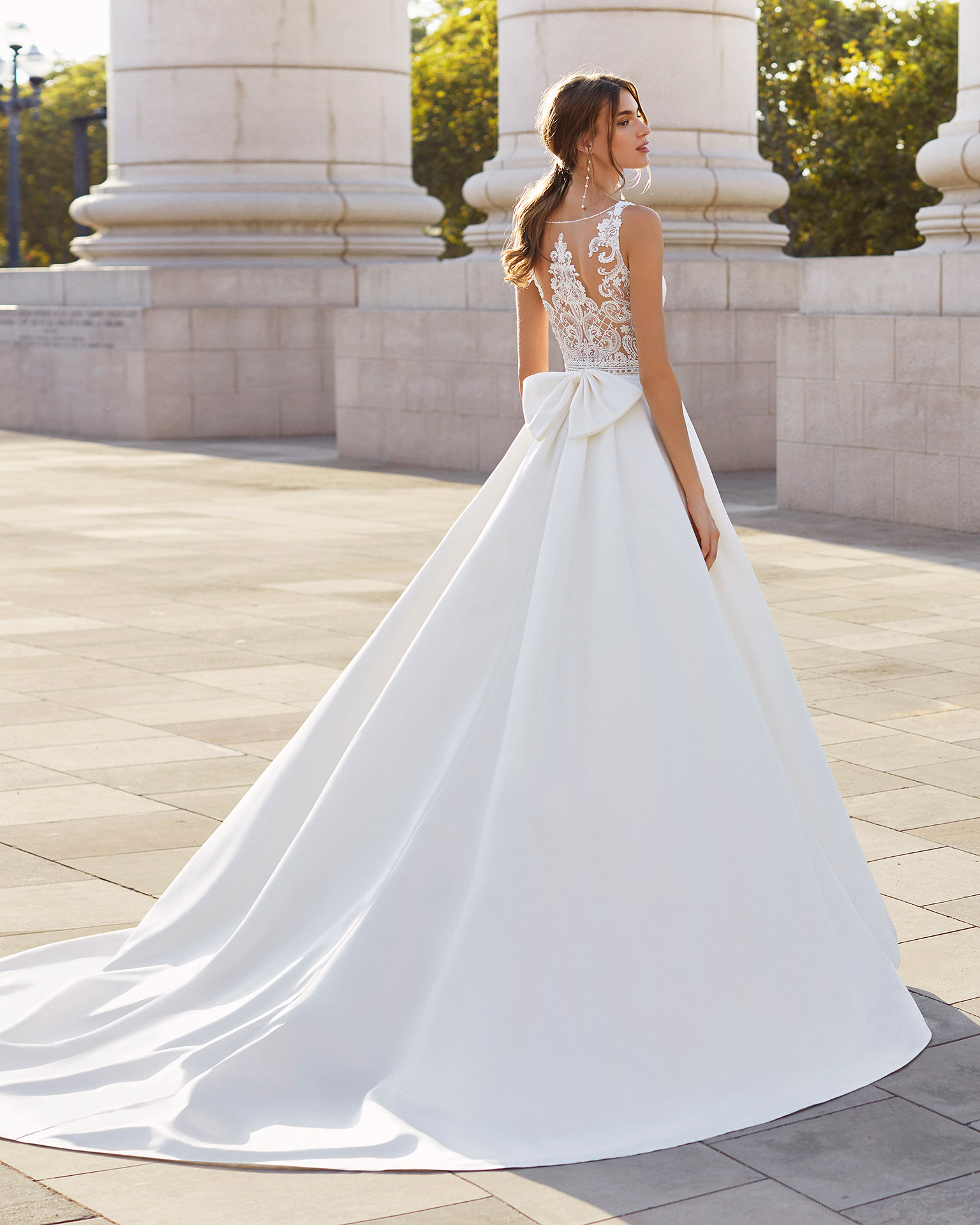 Classic-style wedding dress in satin and beaded lace. Bateau neckline and sheer back in beaded lace with bow. 2021  Collection.