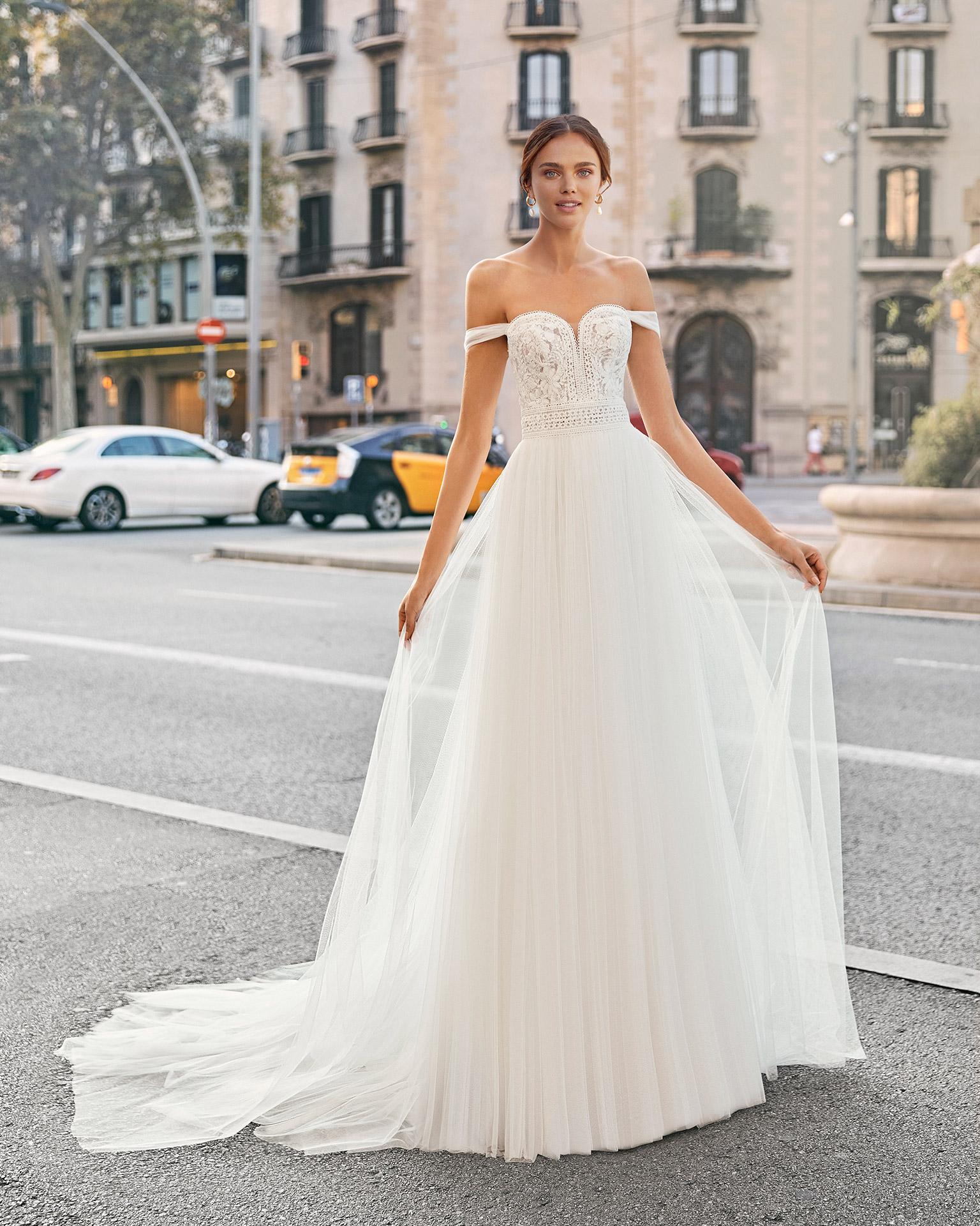 Vestido de novia de corte recto de tul suave, encaje y pedrería. Escote corazón con tirantes bajo hombro. Colección  2021.