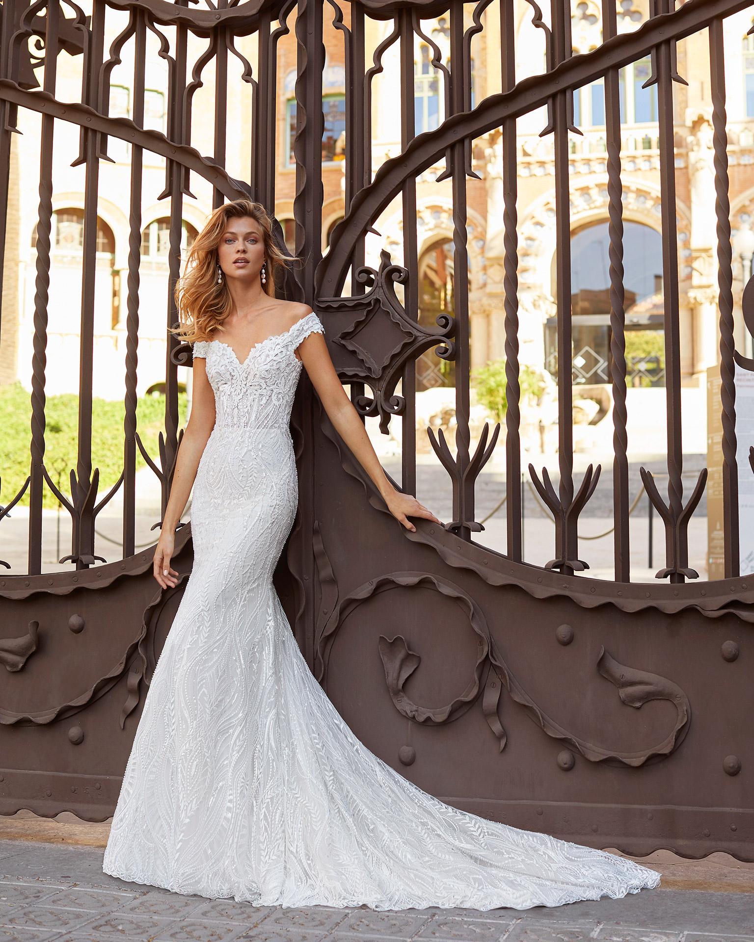 Vestido de novia corte recto de encaje y pedrería. Escote corazón con tirantes bajo hombro. Colección  2021.