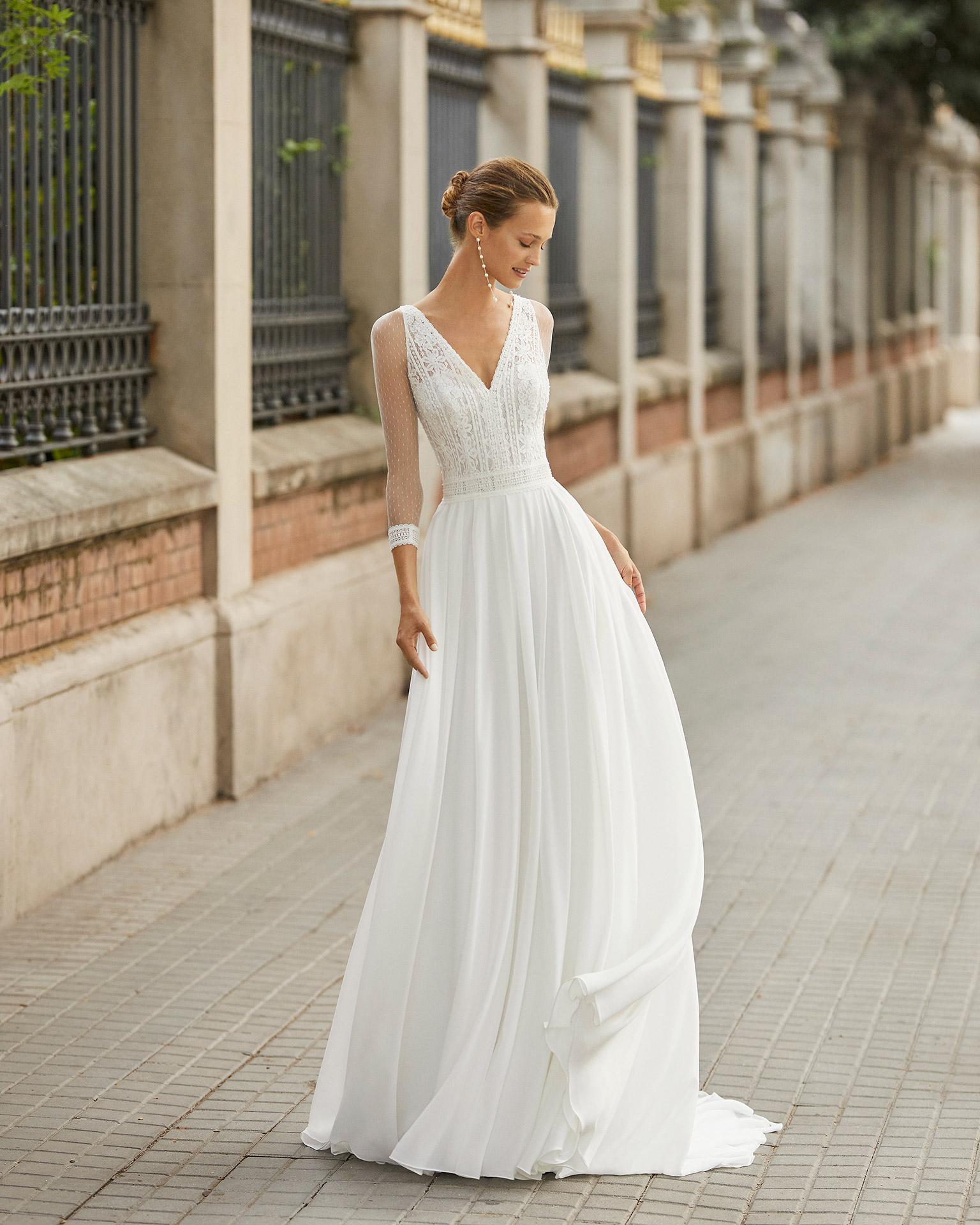 Vestido de novia ligero de georgette, encaje y pedrería. Escote en V, mangas 3/4 y espalda transparente. Colección  2022.
