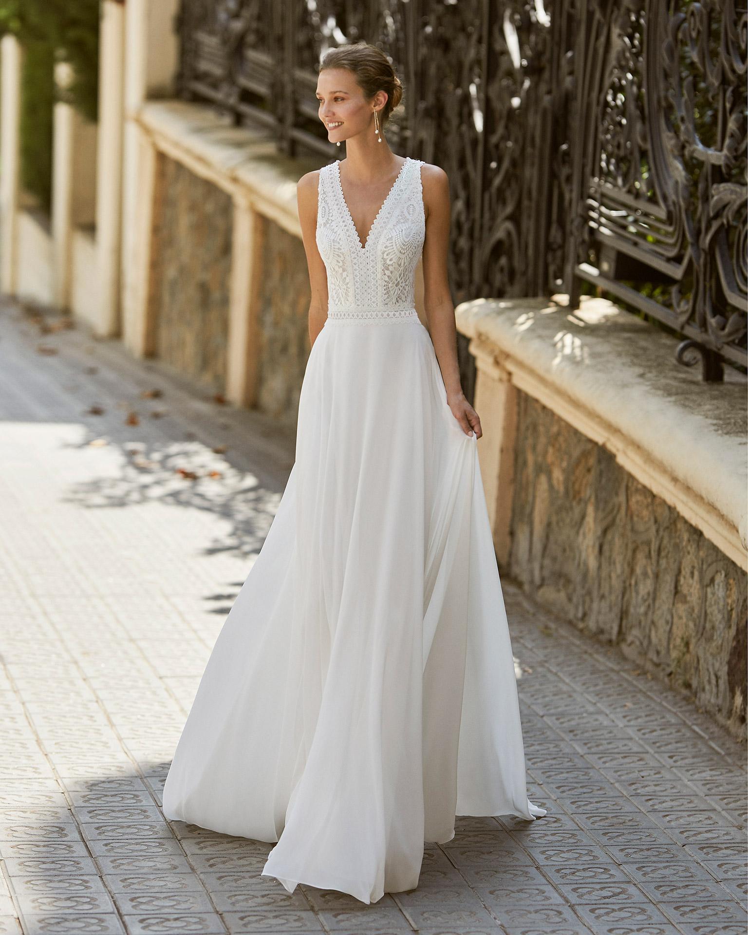 Vestido de novia ligero de gasa, encaje y pedrería en escotes y cintura. Escote en V y espalda abierta. Colección  2022.