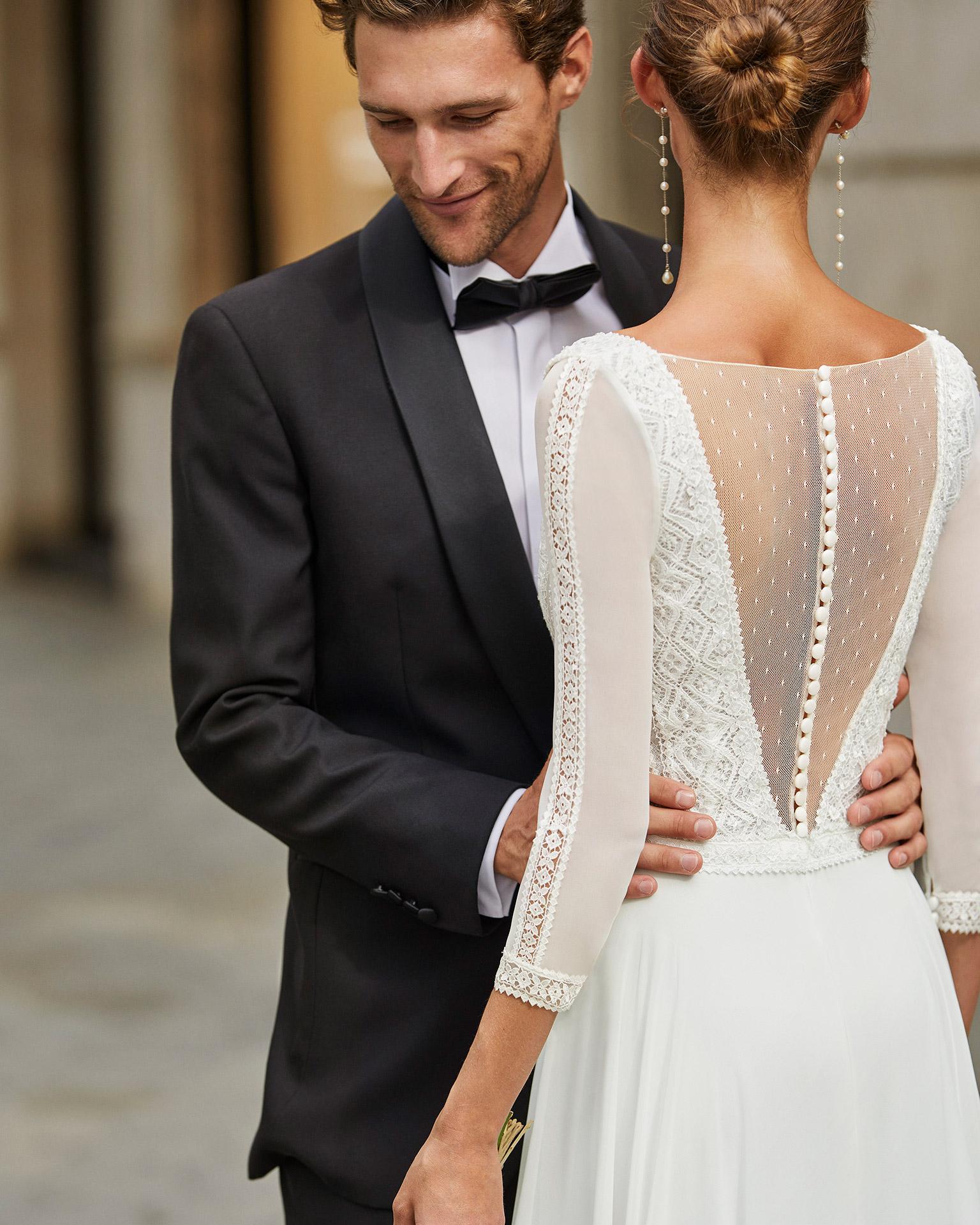 Vestido de novia ligero de georgette, encaje y pedrería. Escote deep plunge, manga 3/4 y espalda en V transparente. Colección  2022.