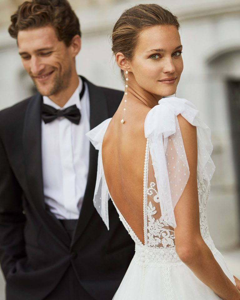 Romantic wedding dress, dot tulle, lace and beaded neckline and waist. Deep-plunge neckline, V-back and dot tulle bows on the shoulders. 2022  Collection.
