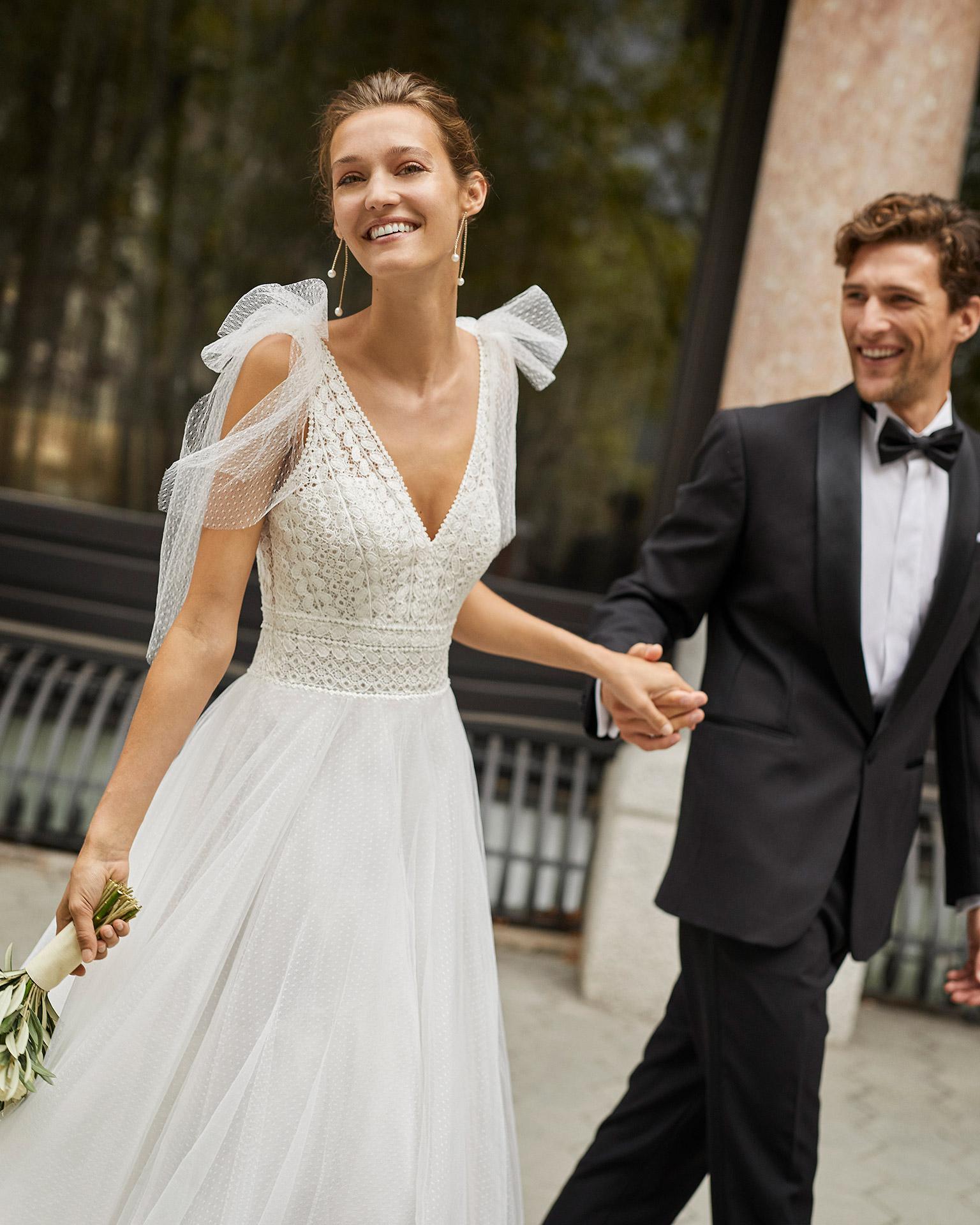 Vestido de novia de estilo romántico, tul plumetti, encaje y pedrería en escotes, sisas y cintura. Escote en V, espalda escotada y lazos en hombros de tul plumetti. Colección  2022.