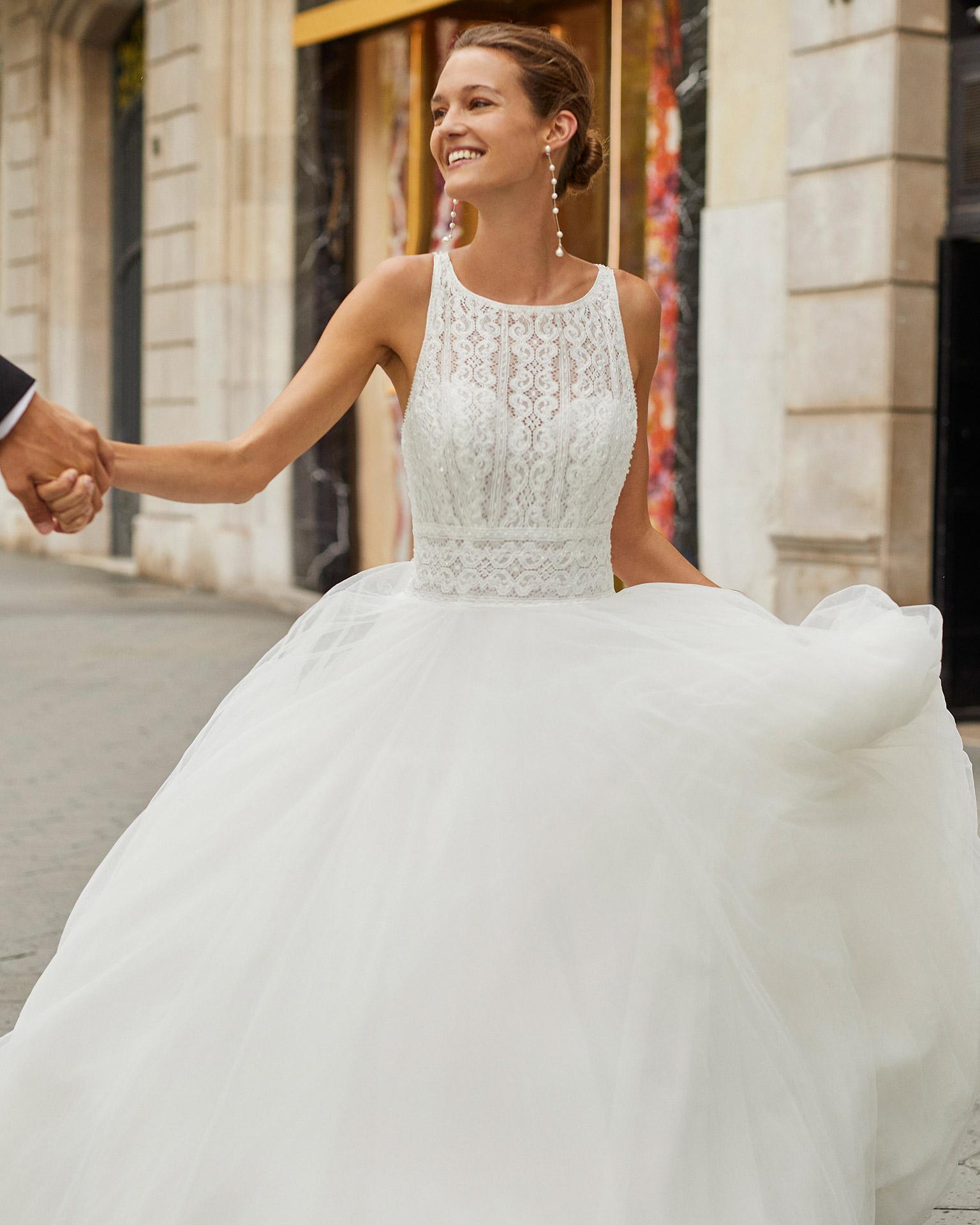 Vestido de novia de estilo romántico, tul, encaje y pedrería. Escote barco y espalda con tirantes cruzados. Colección  2022.