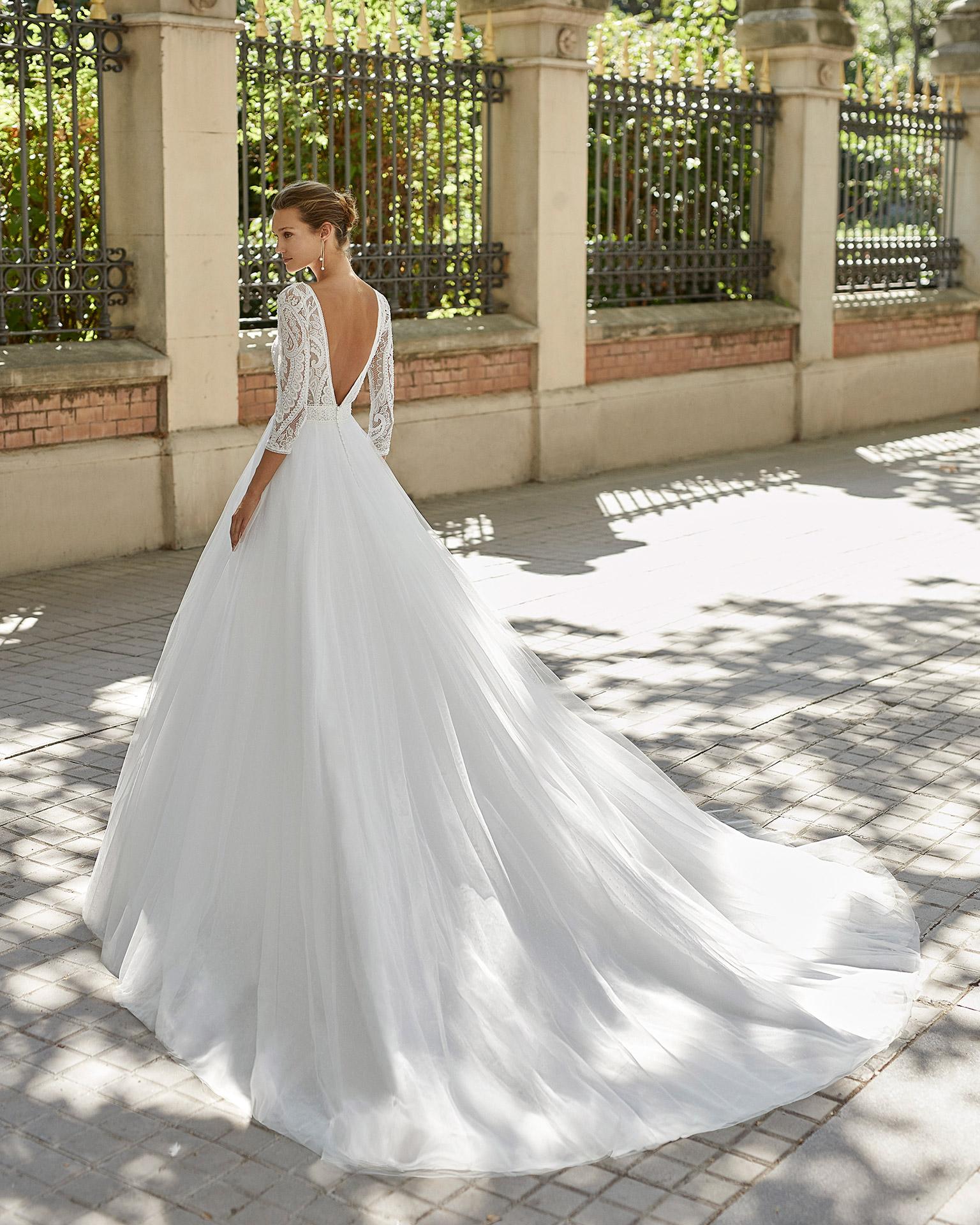 Vestido de novia de estilo romántico, tul plumetti, encaje y pedrería. Escot barco, espalda en V y manga 3/4. Colección  2022.