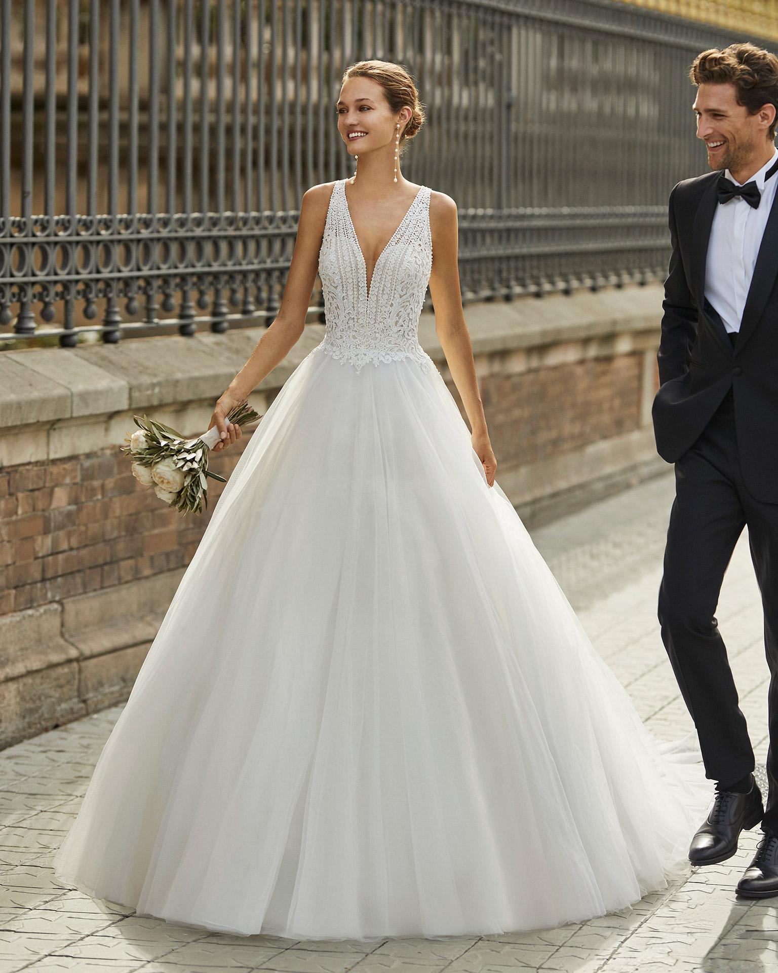 Vestido de novia de estilo princesa, tul, encaje y pedrería. Escote deep plunge y espalda cruzada. Colección  2022.