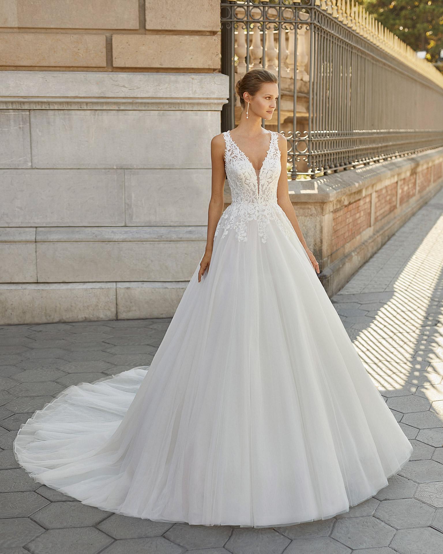 Vestido de novia de estilo romántico, tul, encaje y pedrería. Escote deep plunge y espalda escotada. Colección  2022.