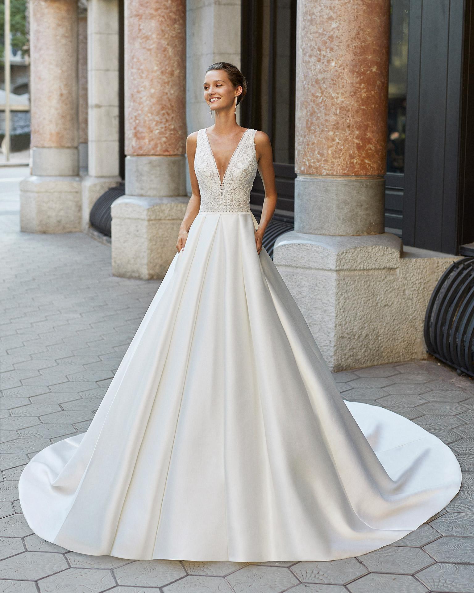 Vestido de novia de estilo clásico, raso, encaje y pedrería. Escote deep plunge y espalda con encaje aplicado. Colección  2022.