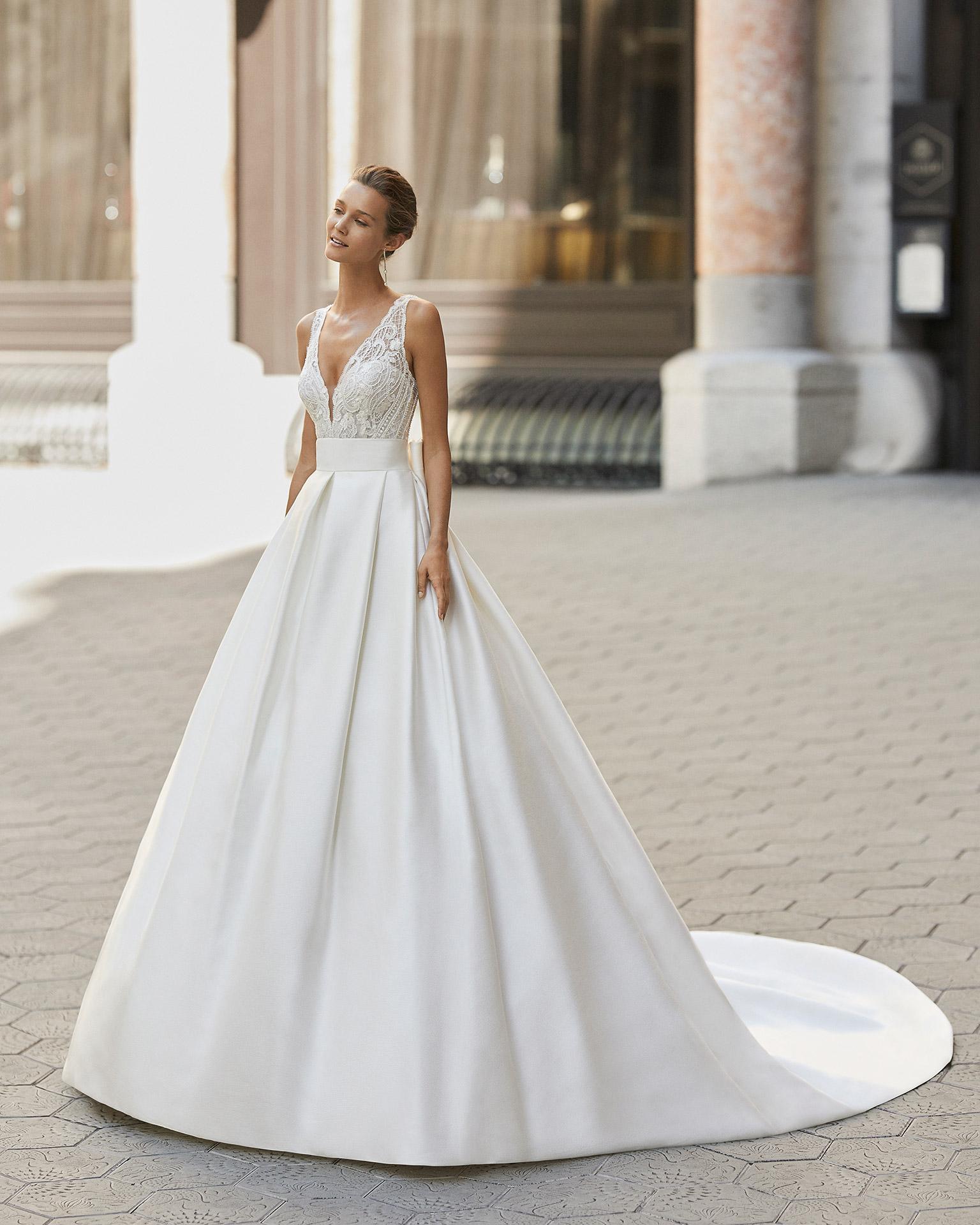 Vestido de novia de estilo clásico, raso, encaje y pedrería. Escote deep plunge y espalda escotada. Colección  2022.