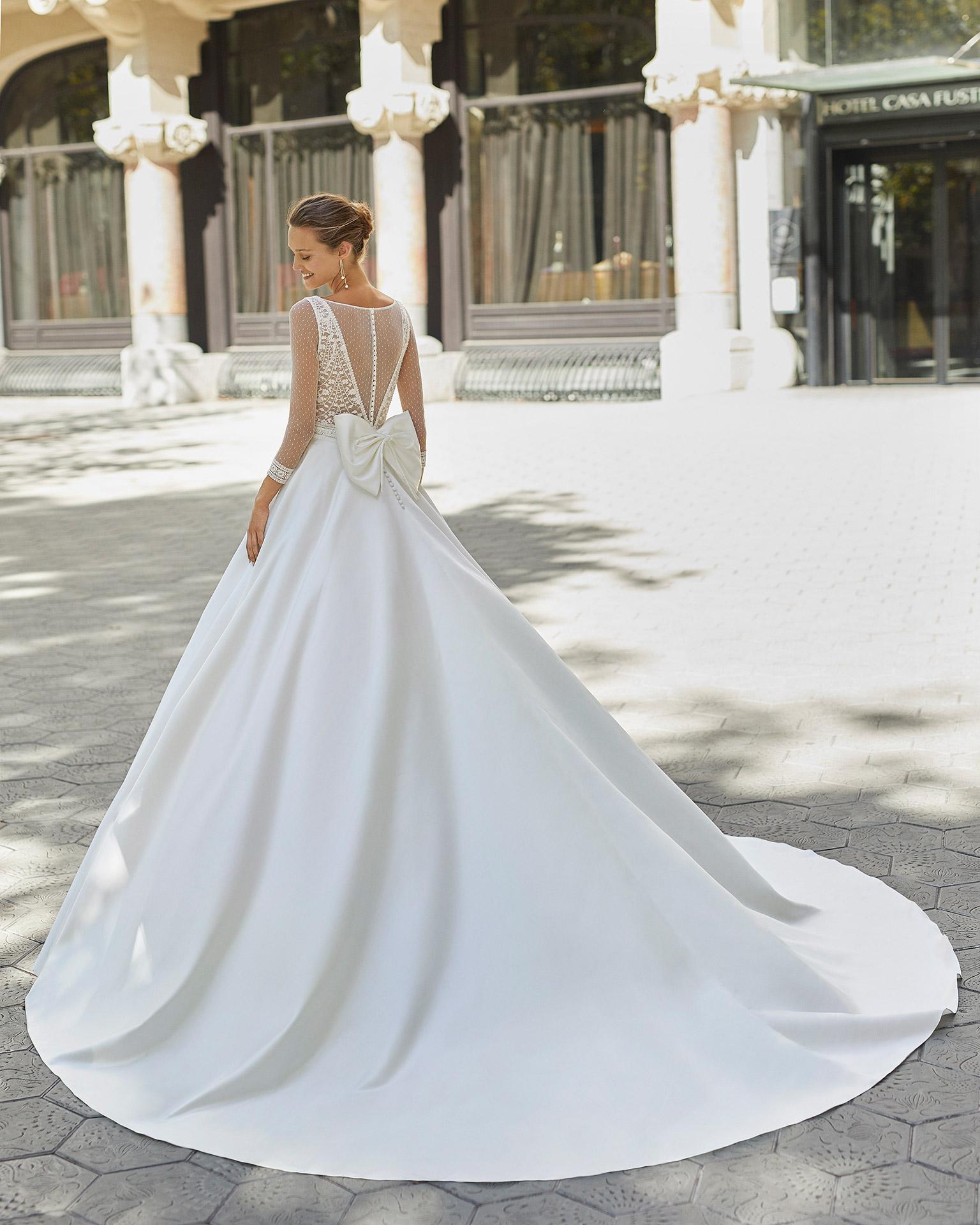 Vestido de novia de estilo clásico, raso, encaje y pedrería. Escote deep plunge, espalda tul plumetti y manga 3/4 tul plumetti. Colección  2022.