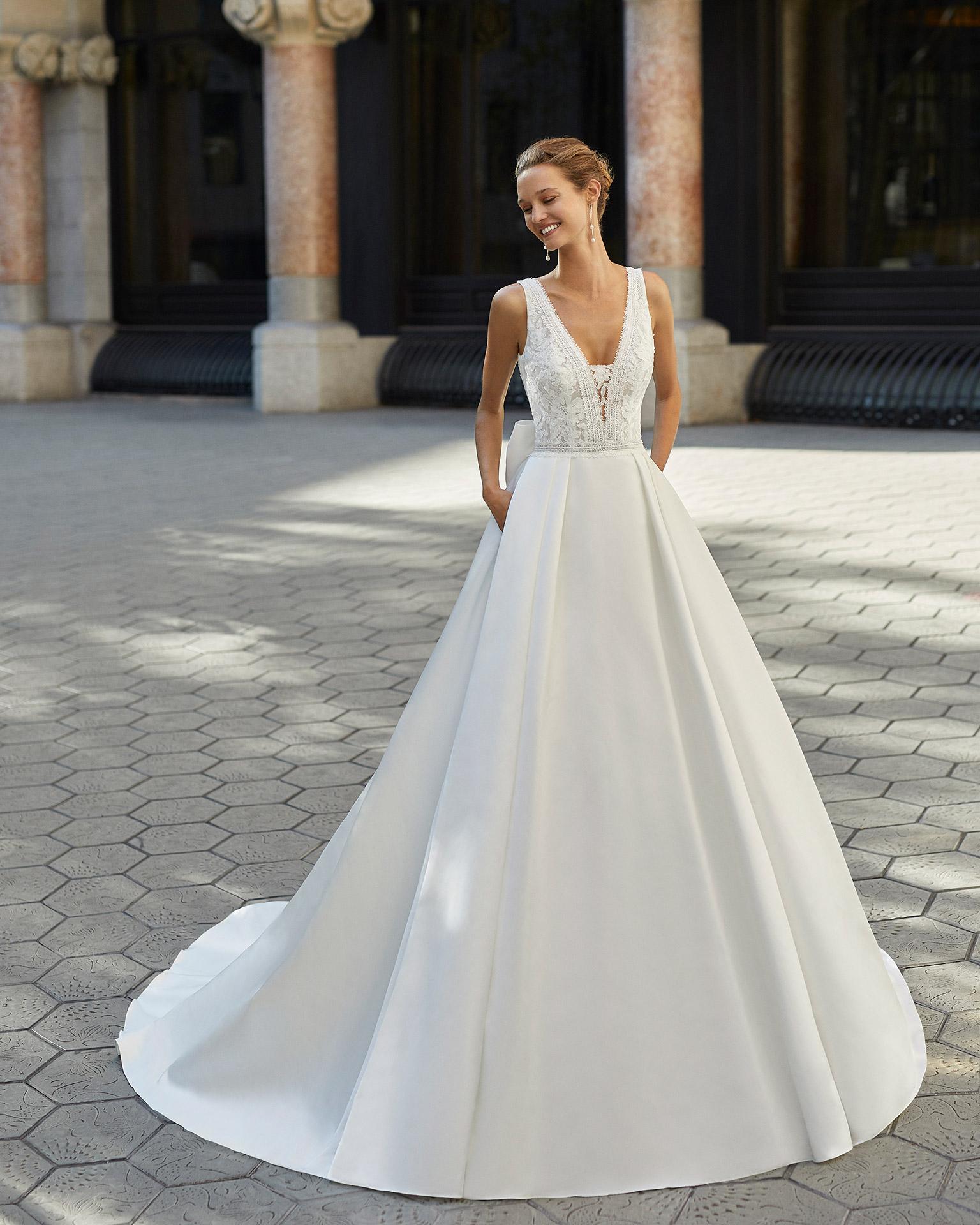 Vestido de novia de estilo clásico, raso, encaje y pedrería en cintura. Escote en V y espalda con encaje aplicado. Colección  2022.