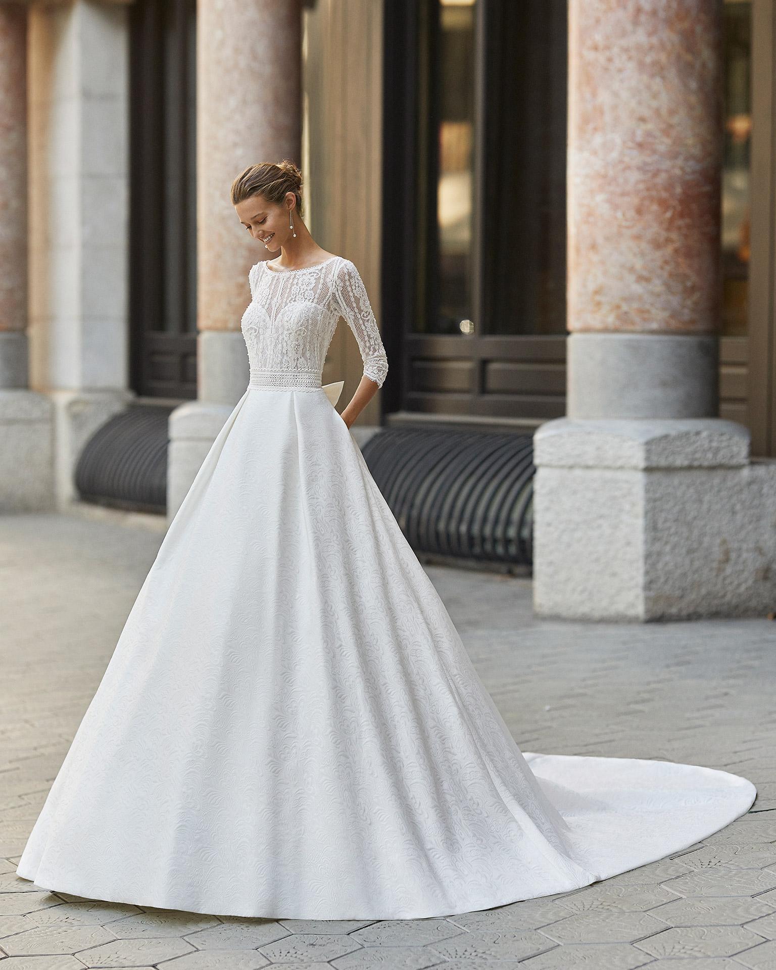 Vestido de novia de estilo clásico, brocado, encaje y pedrería. Escote barco y espalda en V con manga 3/4. Colección  2022.